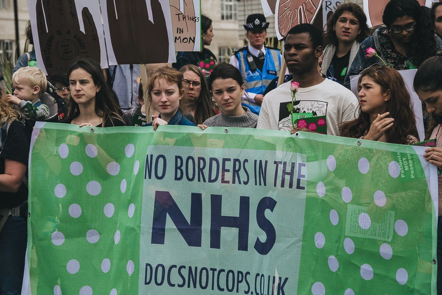 """A group of protesters hold a banner reading """"No borders in the NHS"""""""